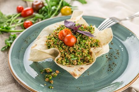 Traditional Arabic Salad Tabbouleh with couscous, tomato and greens in lavash bread bowl on wooden table side view