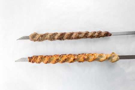 chicken and lamb shish kebab on metal skewer isolated on white background top view