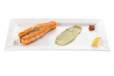 Grilled salmon fillet with lemon and guacamole sauce on white plate isolated on white background side view