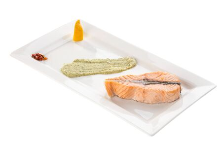 Steamed salmon fillet with lemon and guacamole on white plate isolated on white background side view