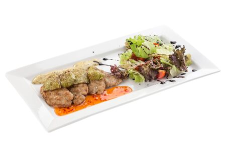Grilled meat with zucchini and fresh salad on white plate isolated on white background side view