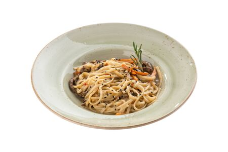 Noodles with beef, vegetables and sesame seeds on grey plate isolated on white background side view