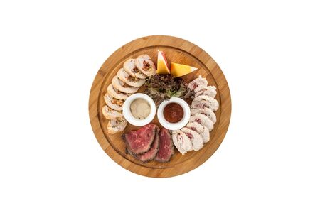 Different appetizer smoked meat and chicken on wooden plate isolated on white background top view