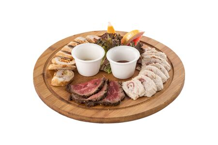 Different appetizer smoked meat and chicken on wooden plate isolated on white background side view