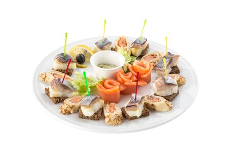 Canapes with smoked fish appetizer platter isolated on white background side view