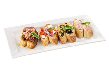 Brushetta set for wine Variety of small sandwiches appetizer on white plate isolated on white background side view 写真素材