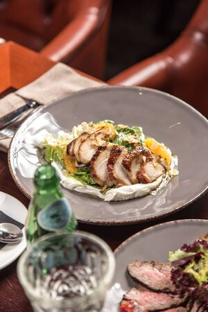 Salad with roasted duck breast and orange with white napkin on wooden table at restaurant side view