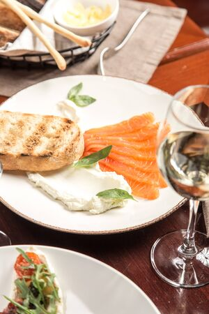 Slices of salmon, cream cheese and grilled bread toast on wooden table at restaurant side view Reklamní fotografie