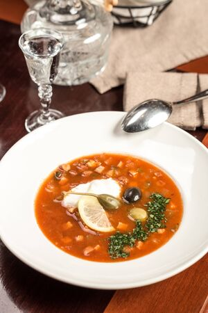 Traditional Russian soup Solyanka with cabbage, olives, lemon and capers on wooden table at restaurant side view Banco de Imagens