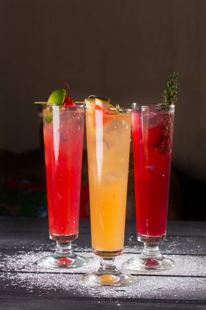 three glasses of fruit red yellow lemonade with ice in highball glasses on black background side view