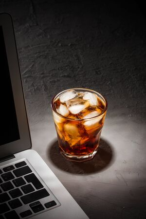 glass of cola with ice and laptop on grey stone table on black background side view 版權商用圖片