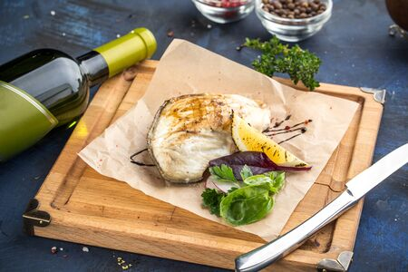 grilled white fish fillet on wooden board with bottle of wine on blue background side view