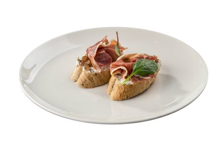 Toast with serrano jamon, prosciutto crudo Italian antipasti with bread bruschetta isolated on white background side view