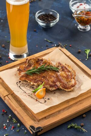 Chicken schnitzel grilled on wooden board with glass of beer on blue background side view Foto de archivo