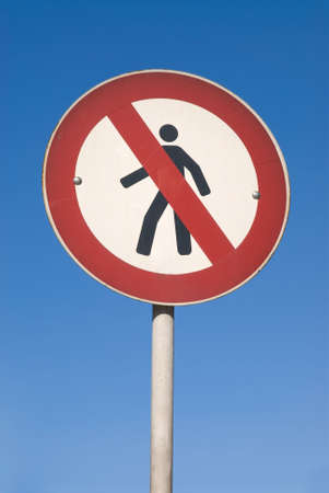 No Walking Sign against blue sky photo