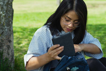 Beautiful college student in a time of rest and reading in the park.