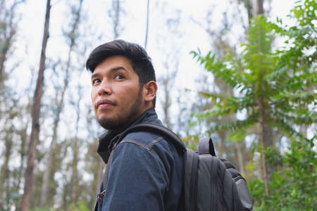 Young man walking in the woods taking selfies. To show your friends.