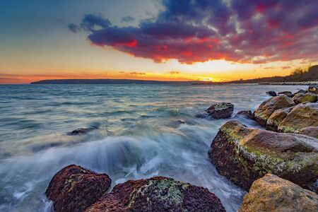 seascapes: Exciting autumn sunset. Beauty sea rocky coast with slow shutter and waves flowing out.Varna, Bulgaria Stock Photo