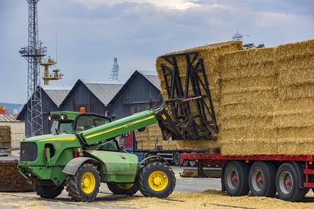 VARNA,BULGARIA September,19,2016: JohnDeere Telescopic handler unloading bales from truck. Day view
