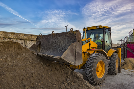 day view of yellow excavator with shovel at construction site
