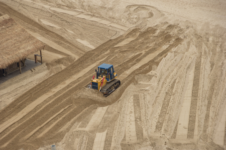 industrial machinery: bulldozer flattens beach sand. top view