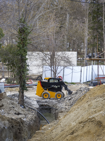 earthwork: day view of mini yellow excavator with shovel in action at construction site Stock Photo