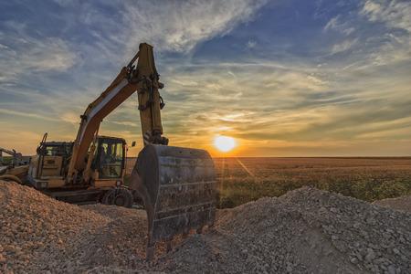 Graafmachine in bouwwerf bij overweldigende zonsondergang Stockfoto