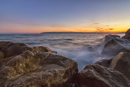 seascapes: Sunset over the sea with splash waves on the rocks