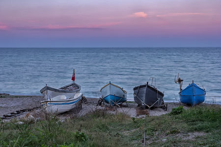 several wooden boats on the sand after sunset