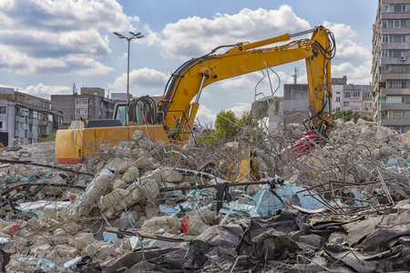 Demolition machine crushing debris of old structure in the city