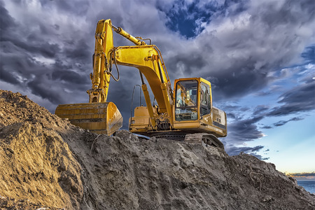 A stopping yellow excavator at an incredibly beautiful sunset Stock Photo