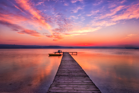 Exciting sunset at shore with wooden pier and boat