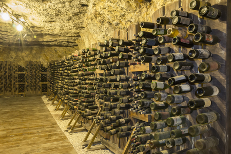 Many old wine bottles stacked on wooden racks in a cellar Imagens