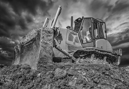 Amazing black and white view of stopped bulldozer and blade into the ground. Wide angle, close up