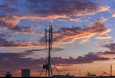 silhouette of GSM transmitters on the roof office building at amazing clouds
