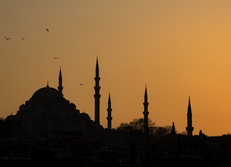 Silhouette of the old town - Sultanahmet mosques in setting sun in Istanbul Turkey. Istanbul old town has many mosques to give a silhouette of minarets Stock Photo