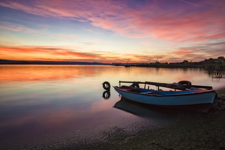 exciting sunset / sunrise on a seashore with fishing boat