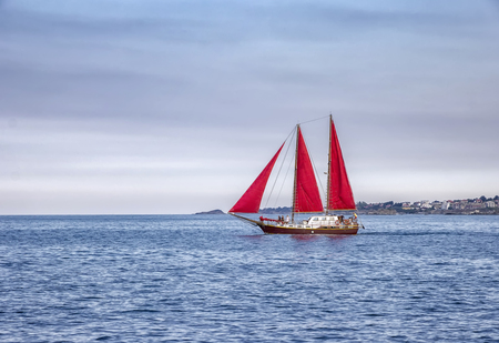 Beautiful composition and mood of a sailing sailboat with red sails