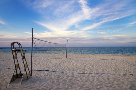 A beach volleyball net on the sandy tropical beach at the sunset / sunrise