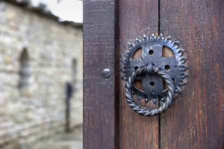 Front wooden door with a knocker, open to blur an inside yard