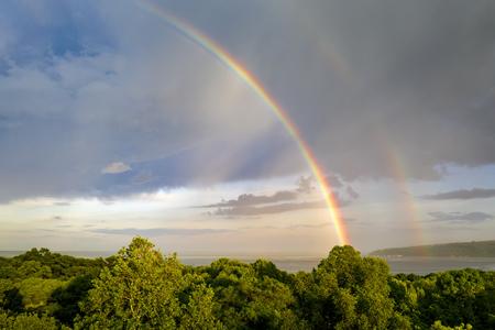 Impresionantes dos grandes arcoíris después de la lluvia sobre el mar.
