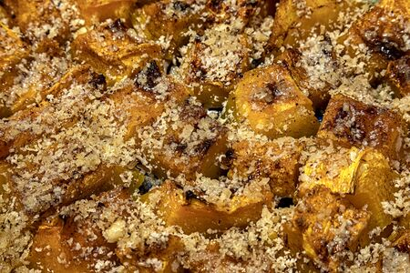 Delicious pieces of roasted pumpkin with crushed walnuts. Close up