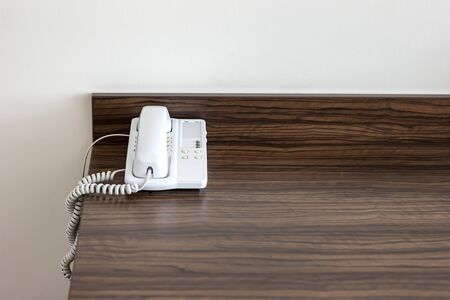 White telephone on the table in a hotel room