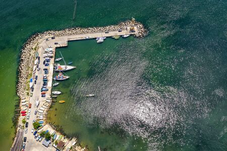 Aerial top view from drone to the seacoast and the marina with boats and yachts. Sea landscape with yachts from above