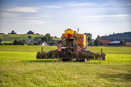 Application of manure on arable farmland with the heavy tractor works at the field in Germany Standard-Bild