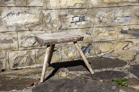 Old small wooden chair in the rural yard near a stone wall. Banco de Imagens