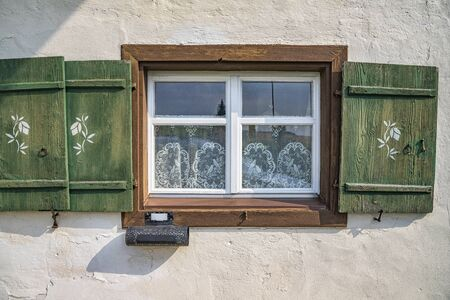 Old ancient wooden window with blinds, curtains and mailbox. Scenic original and colorful view of antique windows in the old city in Germany. No people. Front view. Old fashioned style. Foto de archivo