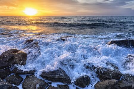 The stunning seascape with the colorful sunrise sky at the rocky coastline of the Black Sea
