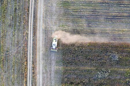 Harvester machine working in the field. Combine harvester agriculture machine harvesting sunflower field. Agriculture. Aerial view. From above.