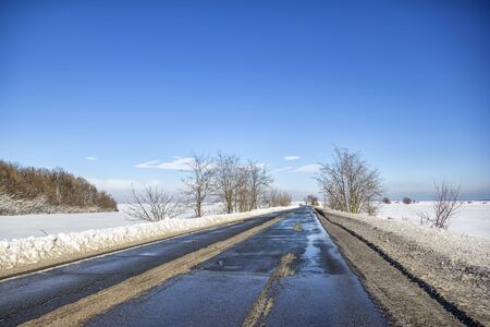 Landscape with a road in the winter with melted snow. The concept of winter travel by car.
